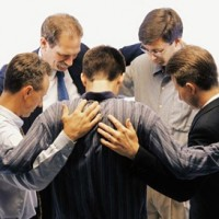 Group of men standing in a circle and praying